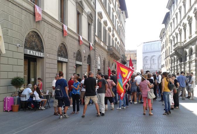 """Due giorni di sciopero, il 30 e il 31 agosto, contro i «licenziamenti» e i contratti precari, indetti dai Cobas. I lavoratori di Eataly protestano contro i tagli al personale, l'organizzazione del lavoro «arbitraria» che «non tiene assolutamente conto delle esigenze dei lavoratori e delle lavoratrici"""" e chiedono stabilizzazione di tutto il personale. Quando il negozio di Firenze ha aperto nel dicembre 2013 erano impiegate 120 persone. Ora sono la metà.  È questo il primo sciopero della catena di store gastronomici. «Il 90% del personale è precario con contratti a termine, di somministrazione e tramite agenzie interinali. In questi mesi 60 contratti alla scadenza non sono stati rinnovati», spiegano i sindacati. Negli ultimi mesi sono 13 i dipendenti rimasti a casa, tre sono in scadenza da qui a ottobre. Sabato oltre ai tre ragazzi con contratto in scadenza hanno manifestato davanti allo store Eataly di via Martelli una cinquantina di persone in solidarietà con i lavoratori. (Ivana Zuliani)"""