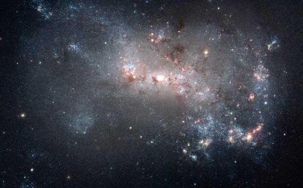 Stelle (accelerate) - L'immagine mostra una piccola galassia irregolare, NGC 4449, molto simile alla Grande Nube di Magellano che orbita intorno alla nostra galassia. Questa galassia sta producendo stelle ad un tasso molto più elevato che in passato. I giovani ammassi stellari (di colore bianco-azzurro) sono visibili in molte regioni. Quelli più giovani, nati meno di 5 milioni di anni fa, sono ancora circondati da gas caldo e polveri cosmiche (di colore rosso). Il gas nei filamenti oscuri, visibili nell'immagine, è freddo. Ma non per molto: il gas sta collassando per formare nuove stelle che si accenderanno fra centinaia di migliaia di anni. (Edvige Corbelli Credito:Hubble Space Telescope) GUARDA LE IMMAGINI SUL SITO DELL'OSSERVATORIO DI ARCETRI