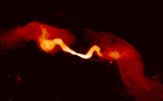 I baffi relativi - Due enormi baffi si propagano in direzioni opposte dal centro della galassia NGC383, dove risiede un enorme buco nero. Sono formati da particelle relativistiche che seguono le linee di un campo magnetico ed emettono onde radio. La foto è stata ottenuta con il radiotelescopio VLA. Inizialmente i due getti sono collimati, ma a distanza di centinaia di migliaia di anni luce dalla galassia, le particelle rallentano e i getti si trasformano in piume larghe. Se guardiamo la stessa zona di cielo con un normale telescopio ottico non siamo in grado di vedere i getti. Al loro posto c'è una catena di 5 galassie. (Edvige Corbelli Credito: NRAO/AUI)
