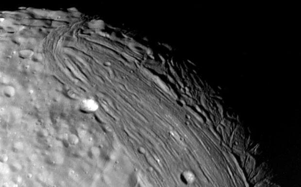 Miranda di ghiaccio - Miranda, il più interno dei satelliti di Urano, ripreso dalla sonda Voyager 2 nel 1986. La sua superficie (il suo diametro è poco più di un decimo di quello della Luna) è probabilmente costituita da ghiaccio di acqua ed è molto complessa e variegata. Per esempio, nella parte centrale della foto si ha una regione relativamente vecchia e coperta da crateri da impatto. Più in alto a destra si notano una serie di canyons, profondi fino a 20 chilometri, indicanti una più recente attività geologica, forse prodotta dall'attrito mareale con Urano. (Gian Paolo Tozzi Crediti: NASA/JPL) GUARDA LE IMMAGINI SUL SITO DELL'OSSERVATORIO DI ARCETRI