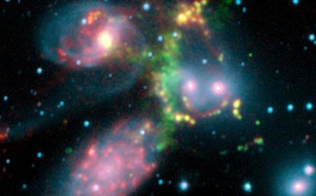 Quartetto d'archi - Il gruppo di cinque galassie visibile nella foto è noto come Quintetto di Stephan ed è stato scoperto nel 1877 nella costellazione del Pegaso. Studi recenti hanno però mostrato che una galassia, la più luminosa in basso a sinistra, non fa parte del gruppo ma è molto più vicina a noi. Le altre quattro, giallo-rosa del nucleo, stanno interagendo violentemente fra loro. Il gigantesco arco al centro (di colore verde) è il risultato di una violenta onda d'urto che riscalda le molecole di idrogeno e le rende visibili nell'infrarosso. Un vero e proprio quartetto musicale di archi che suona nel cosmo! (Edvige Corbelli Credito: NASA/JPL/MPI/Appleton) GUARDA LE IMMAGINI SUL SITO DELL'OSSERVATORIO DI ARCETRI